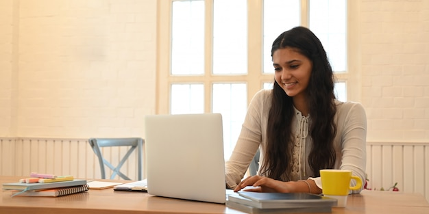 A university student is learning lessons online while sitting at the wooden working desk. Premium Photo