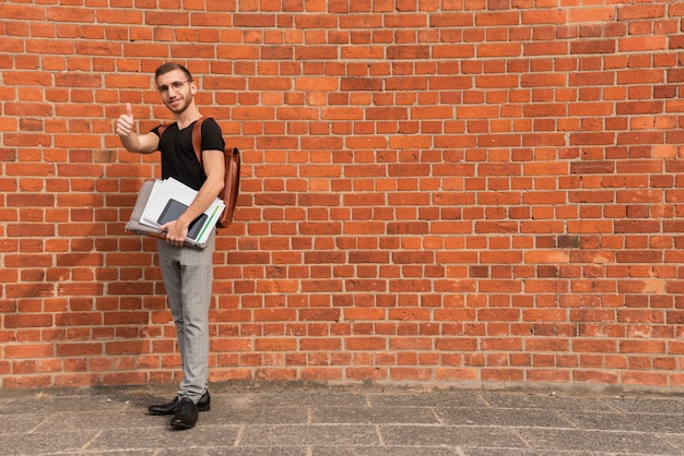 University student standing in front of a brick wall copy space background Free Photo