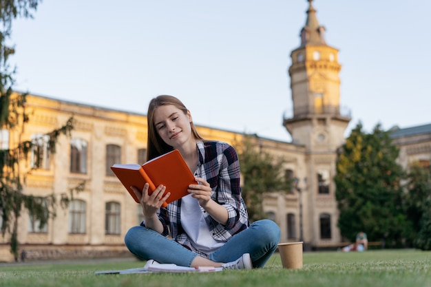 University student studying, reading a book, learning language, exam preparation, sitting on grass, education concept Premium Photo