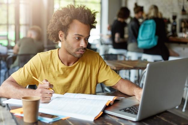 Studente universitario con pelle scura e acconciatura africana seduto al bar che lavora con libri e taccuino mentre si prepara per l'esame che trova le informazioni necessarie in internet con uno sguardo serio Foto Gratuite