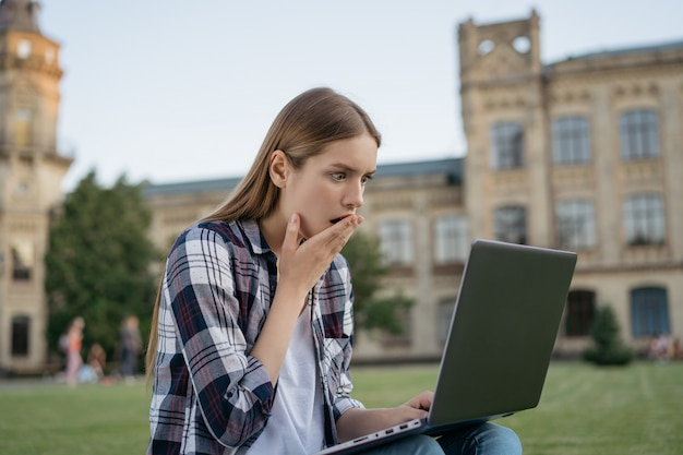 Студент университета с шокированным испуганным лицом читает плохие новости, провал экзамена. женщина фрилансер, использующая ноутбук, она пропустила срок Premium Фотографии