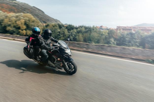 Неизвестная пара байкеров, путешествующая по дороге на мотоцикле Premium Фотографии