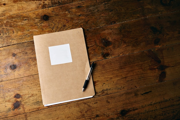 ラベルのないクラフトノートと古い織り目加工の木製テーブルの上のプラスチックの黒いペン 無料写真