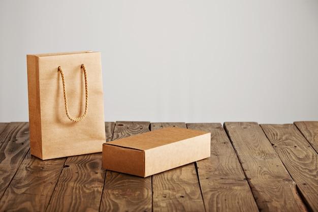 素朴な木製のテーブル、白い背景で隔離の段ボールの空白のボックスの横にあるラベルのないクラフト紙袋 無料写真