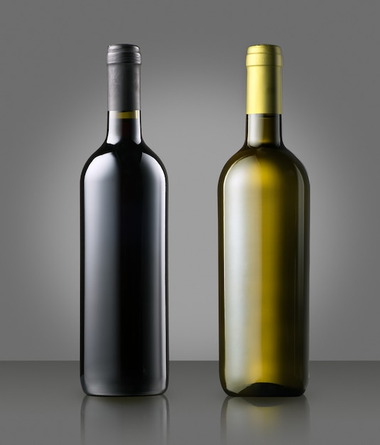 Unlabelled red and white wine bottles on gray Premium Photo