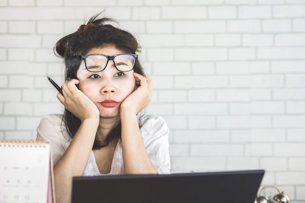 Unmotivated asian female worker at workplace Premium Photo