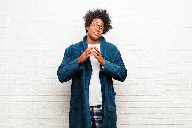 若い黒人男性のパジャマを着て陰謀と陰謀、不正なトリックとチートを考えて、unningなレンガの壁を裏切る Premium写真