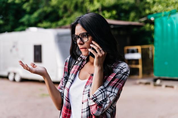 朝の電話で話している流行のメガネで不機嫌なエレガントな女性。路上で悲しそうな表情でポーズをとる魅力的な女の子の屋外ショット。 無料写真