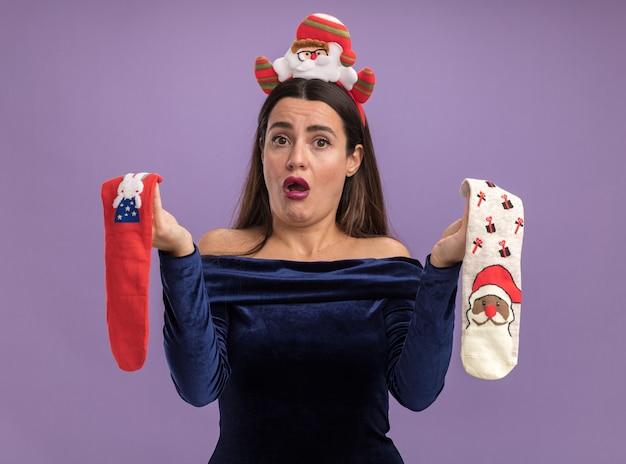 Недовольная молодая красивая девушка в синем платье и рождественском обруче для волос держит рождественские носки на фиолетовом фоне Бесплатные Фотографии