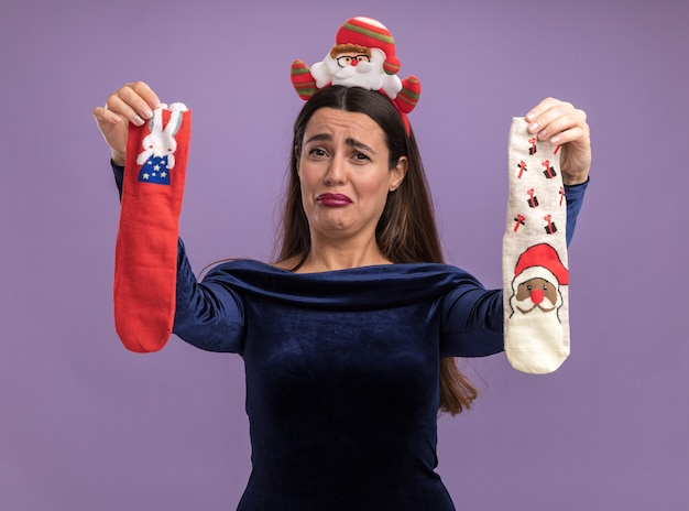 Недовольная молодая красивая девушка в синем платье и рождественском обруче для волос, протягивая рождественские носки перед камерой, изолированной на фиолетовом фоне Бесплатные Фотографии