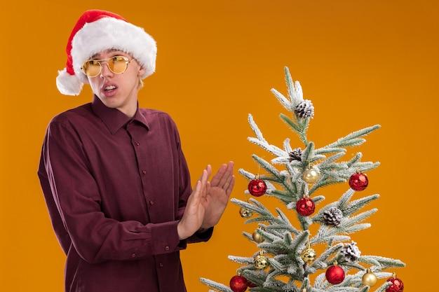 Il giovane biondo dispiaciuto che indossa il cappello e gli occhiali della santa che sta vicino all'albero di natale decorato che guarda al lato che fa il gesto di rifiuto isolato su fondo arancio Foto Gratuite