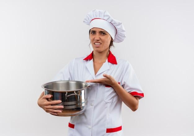 不機嫌そうな若い女性料理人がシェフの制服を持って、コピースペースのある孤立した白い壁に鍋を手で指しています 無料写真