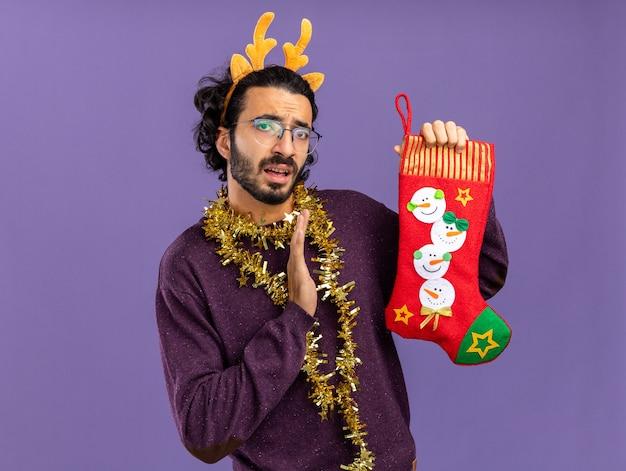Недовольный молодой красивый парень в рождественском обруче для волос с гирляндой на шее, держащий рождественские носки, протягивающий руку в носках, изолированные на синем фоне Бесплатные Фотографии
