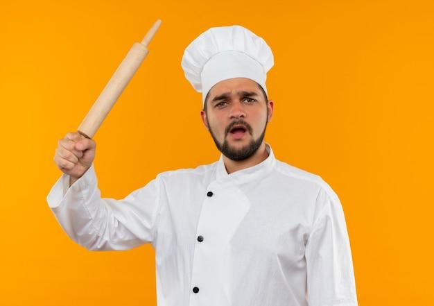 Недовольный молодой мужчина-повар в униформе шеф-повара поднимает скалку, изолированную на оранжевом пространстве Бесплатные Фотографии