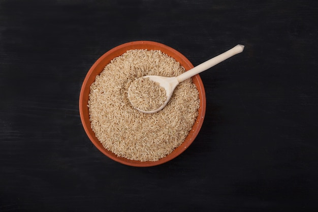 Unpolished rice with a wooden spoon in a clay bowl on a black background Premium Photo