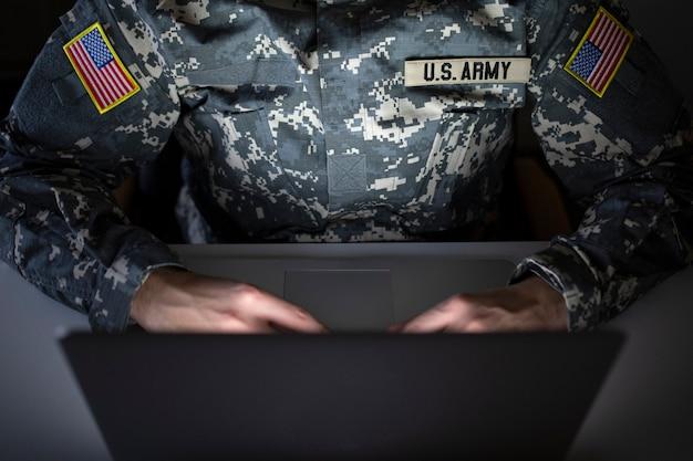Irriconoscibile soldato americano in uniforme militare utilizzando il computer nella comunicazione - centro di intelligence per la sorveglianza e la protezione delle frontiere Foto Gratuite