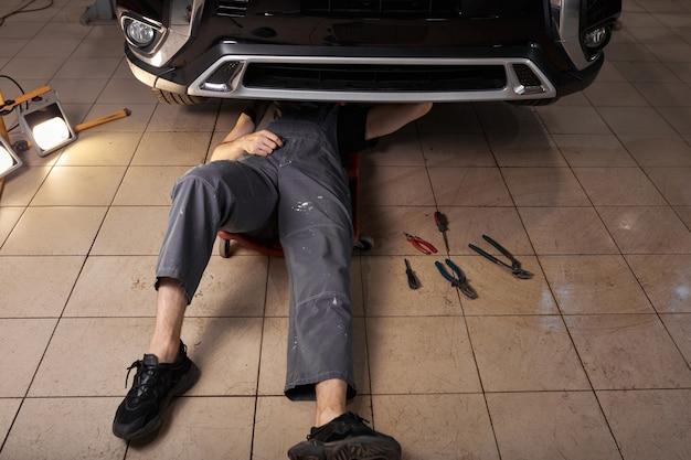 인식 할 수없는 자동차 정비사가 누워서 차 밑에서 일하고 있습니다. 프리미엄 사진