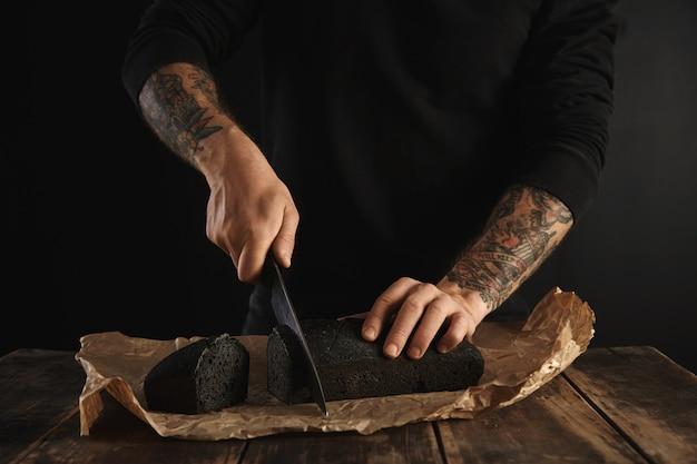 Неузнаваемый пекарь с татуированными руками нарезал большим главным ножом свежеиспеченный домашний угольный хлеб на крафт-бумаге на деревянном деревенском столе Бесплатные Фотографии