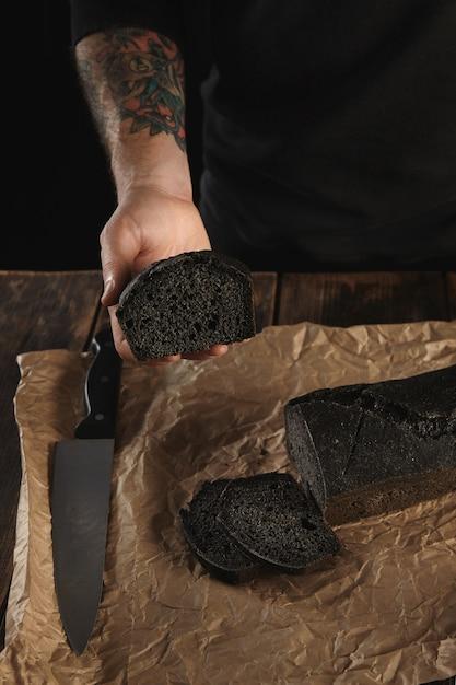 Il panettiere irriconoscibile con le mani tatuate mostra il pezzo di pane al carbone fatto in casa appena sfornato, il grande coltello principale vicino alla carta del mestiere sul tavolo rustico in legno pronto per la vendita Foto Gratuite