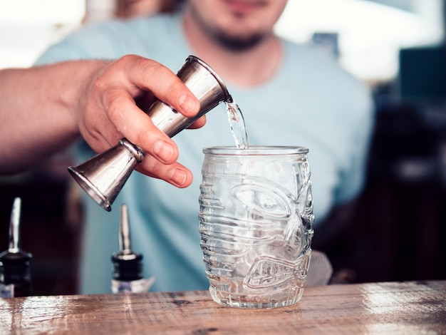 Unrecognizable barkeeper pouring alcohol in glass Free Photo