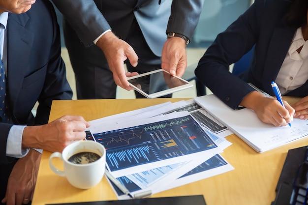До неузнаваемости бизнес-партнеры, работающие со статистическими диаграммами. бизнесмен, держащий таблетку. деловая женщина профессионального содержания, делая заметки для статистики. концепция коммуникации и партнерства Бесплатные Фотографии