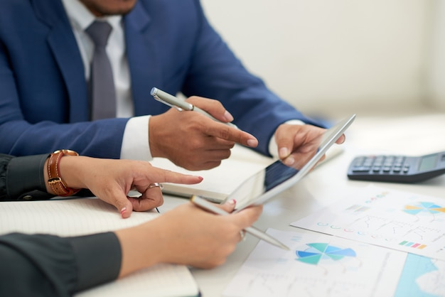 Unrecognizable business people sitting at meeting with charts, looking and pointing at tablet Free Photo