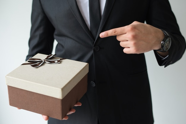 До неузнаваемости бизнесмен держит коричневую подарочную коробку Бесплатные Фотографии
