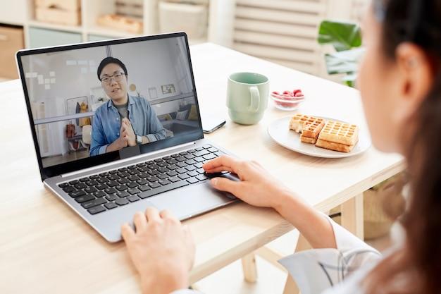 그녀의 노트북에서 온라인 기술을 사용하여 아시아 남자와 일하는 인식 할 수없는 사업가 프리미엄 사진
