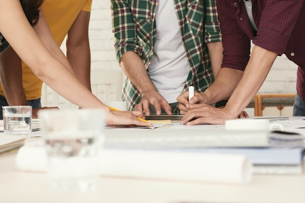Unrecognizable casually dressed people standing around table and brainstorming Free Photo