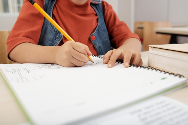 Unrecognizable child sitting at desk and drawing in copybook with pencil Free Photo