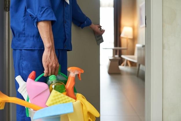 도구와 세제를 사용하여 호텔 방으로 들어가는 인식 할 수없는 청소기 무료 사진