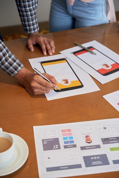 Irriconoscibili colleghi in piedi al tavolo e guardando progetti di design Foto Gratuite