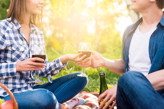 Unrecognizable couple having romantic moment outside with wine Free Photo