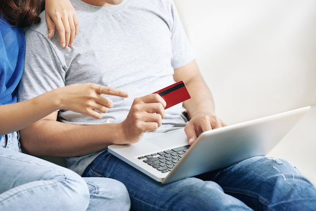 Unrecognizable couple sitting on couch with laptop and man holding credit card Free Photo