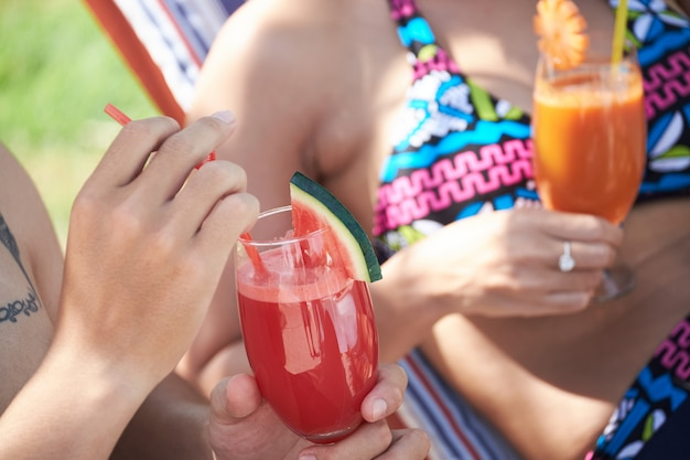Unrecognizable couple in swimsuits enjoying beverages at luxurious resort Free Photo