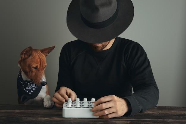 Musicista creativo irriconoscibile con bellissime manopole a rotazione sul suo controllo del mixer midi e cane curioso Foto Gratuite
