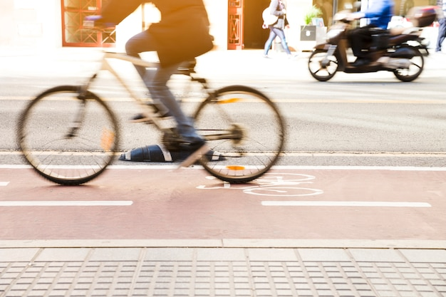 Unrecognizable cyclist riding a bike on bicycle lane through city street Free Photo