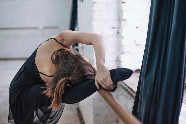 Unrecognizable dancer exercising near barre Free Photo
