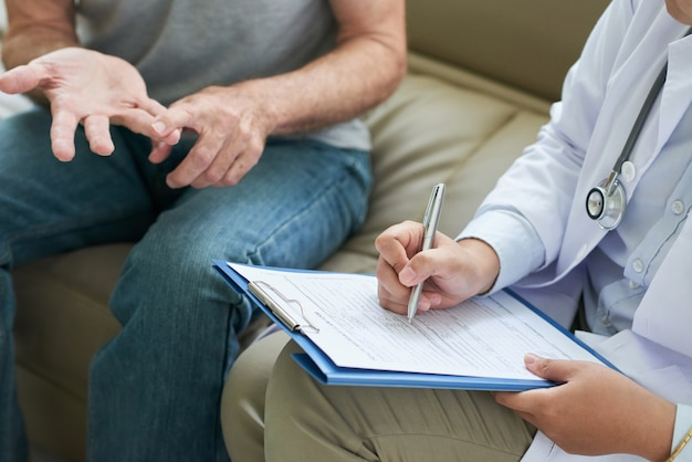 Unrecognizable doctor talking to patient at home and making notes Free Photo