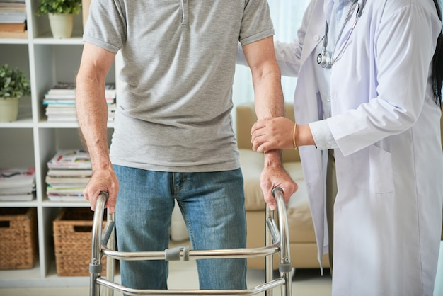 Unrecognizable female doctor helping male patient walk with walking frame Free Photo