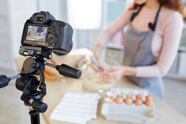 Unrecognizable female food blogger cooking bakery dough on camera, horizontal shot Premium Photo