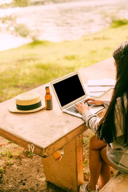 Unrecognizable female using laptop outside near lake Free Photo