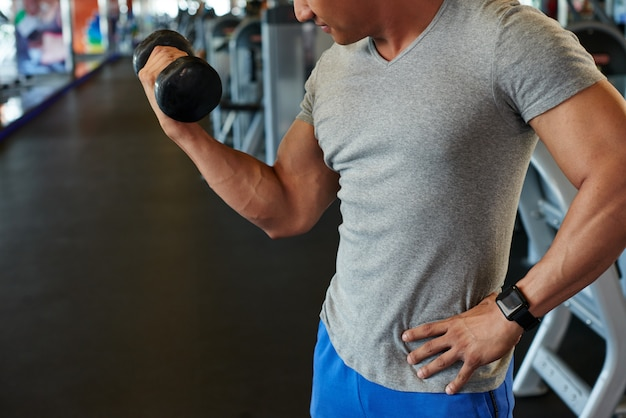Unrecognizable fit man doing bicep curl with barbell in gym Free Photo