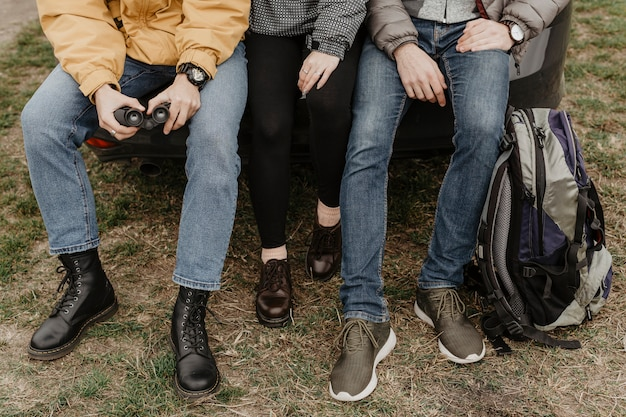 Unrecognizable friends sitting together outdoors Free Photo