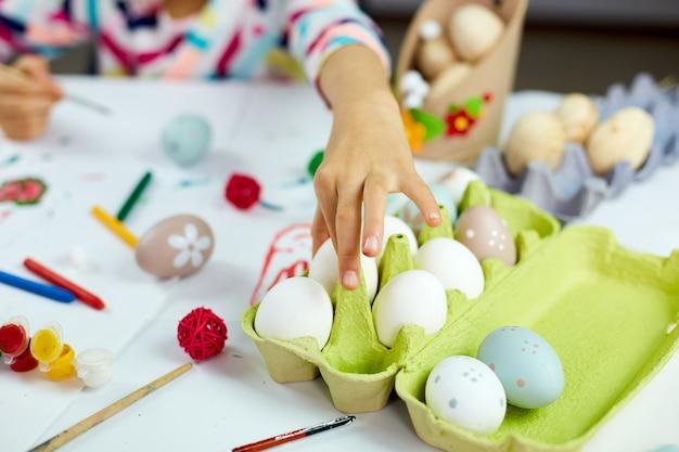 인식 할 수없는 어린 소녀는 계란, 그림, 집에서 브러시 계란으로 그림을 가져갑니다. 부활절을 준비하는 아이, 재미와 축하 잔치. 행복한 부활절, Diy 프리미엄 사진