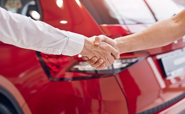 인식 할 수없는 남성 고객 및 관리자가 현대 자동차 대리점에서 빨간색 차량에 악수 프리미엄 사진