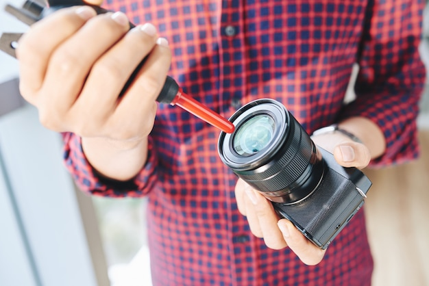 Unrecognizable male photographer cleaning camera lens with air blower Free Photo