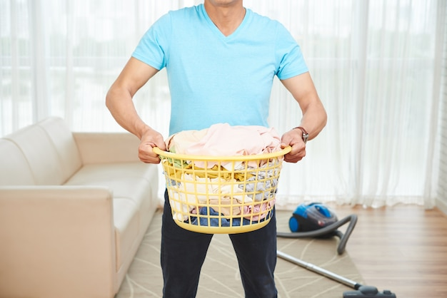 Unrecognizable man carryingfull laundry basket at home, and vacuum cleaner on floor Free Photo