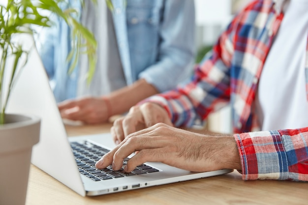 Неузнаваемый человек-фрилансер и его партнерские клавиатуры на портативном компьютере, работают удаленно Бесплатные Фотографии