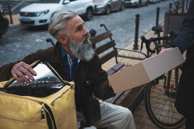 배달 할 수석 택배 골판지 상자 패키지를주는 인식 할 수없는 남자 프리미엄 사진